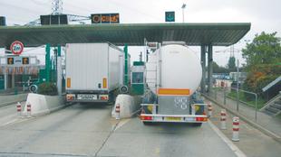 Dos transportistas atraviesan un peaje