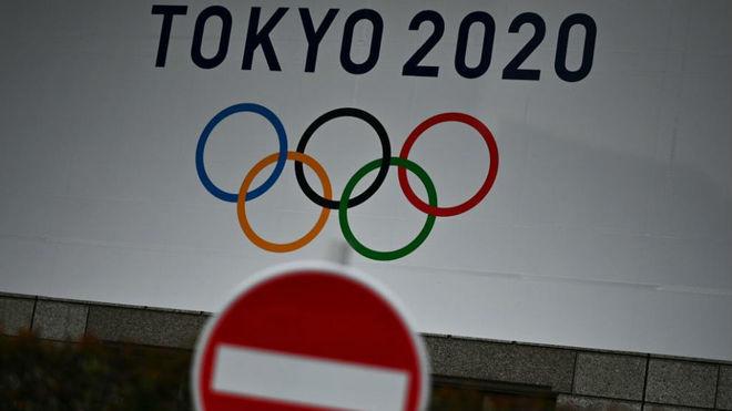 Una señal de prohibido junto a un cartel de los Juegos Olímpicos.