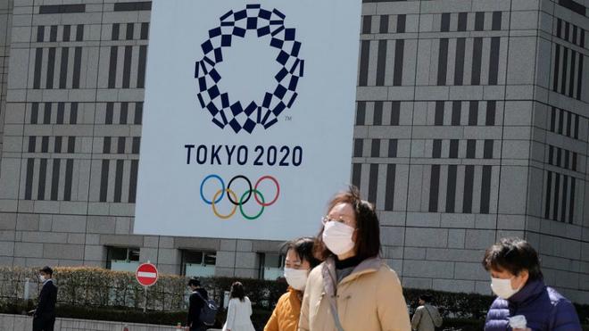 Un enorme cartel con el logo de los Juegos en un edificio...