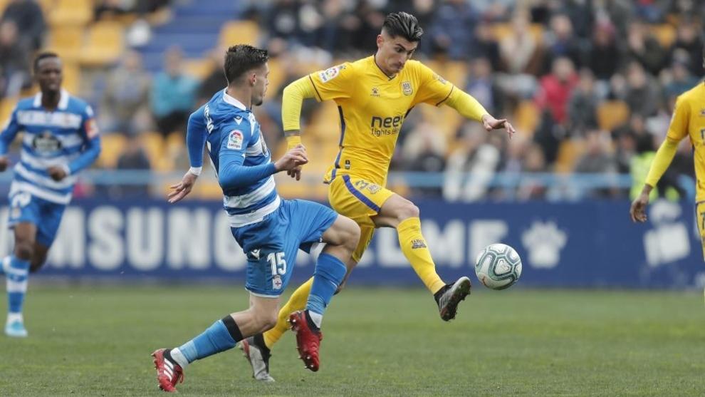 Perea disputa con Montero el balón durante el partido Alcor-Dépor
