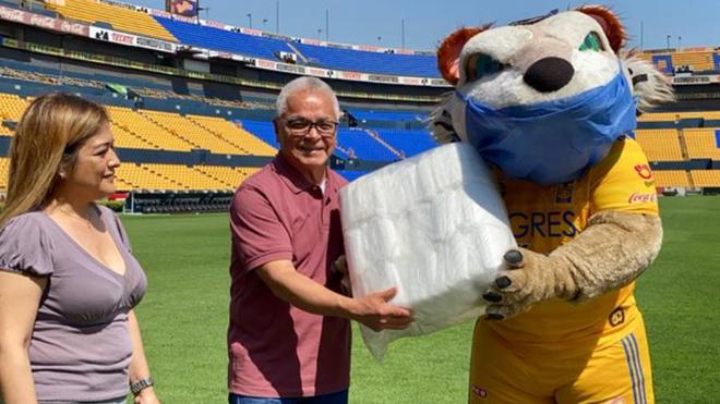 El Tigre entrega un paquete de cubrebocas.