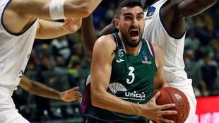 Jaime Fernández entra a canasta entre dos rivales.