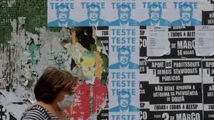 Una mujer en Brasil pasa por delante de carteles con la imagen del...