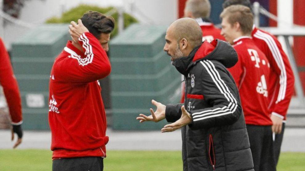 Pep Guardiola dialoga con Claudio Pizarro durante un entrenamiento.