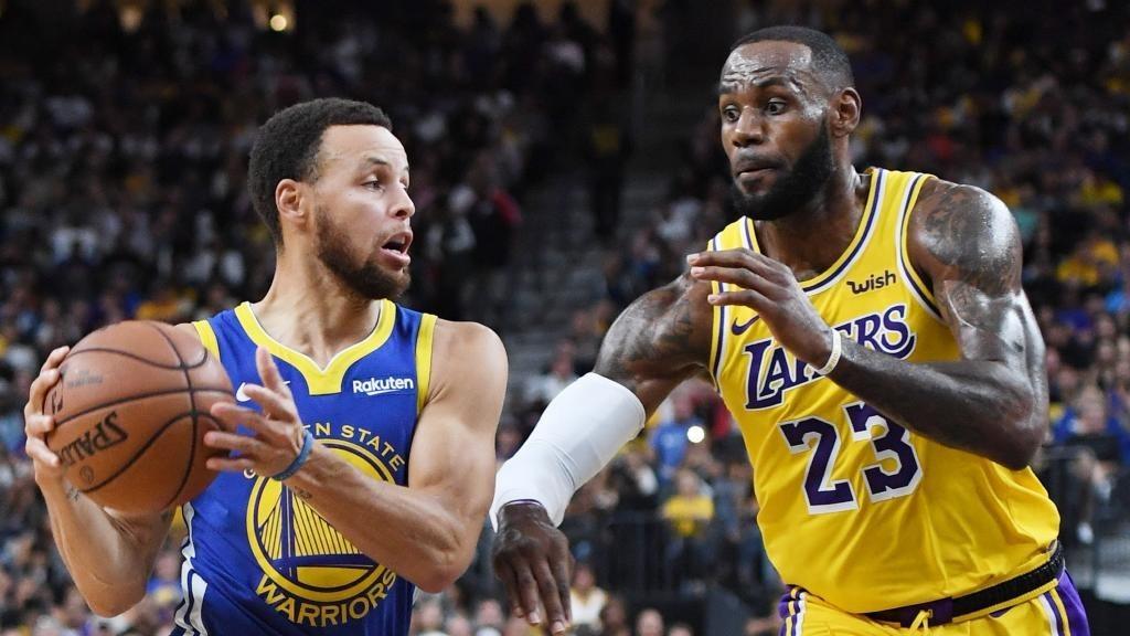 Stephen Curry trata de superar la defensa de LeBron James.