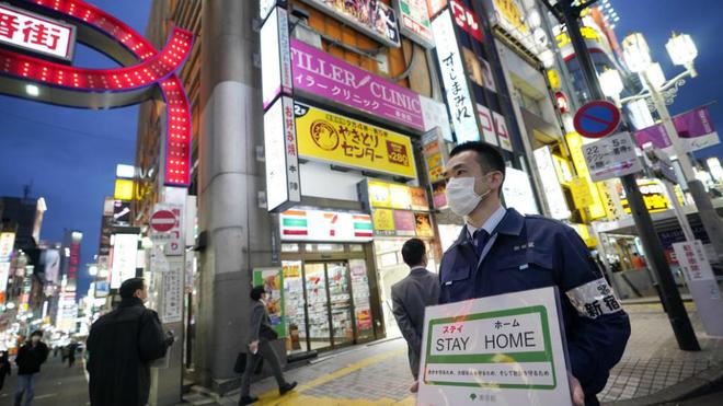 Un empleado municipal de Tokio pidiendo el pasado viernes a la gente...