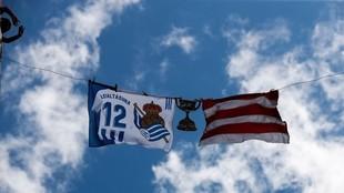 Una bandera de la Real Sociedad y otra del Athletic, junto a una Copa...