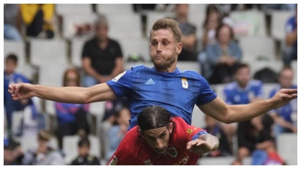 Carlos Hetnández salta para alzanzar el balón ante la presencia del...