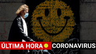 Coronavirus en España, última hora: Una mujer camina con la imagen...