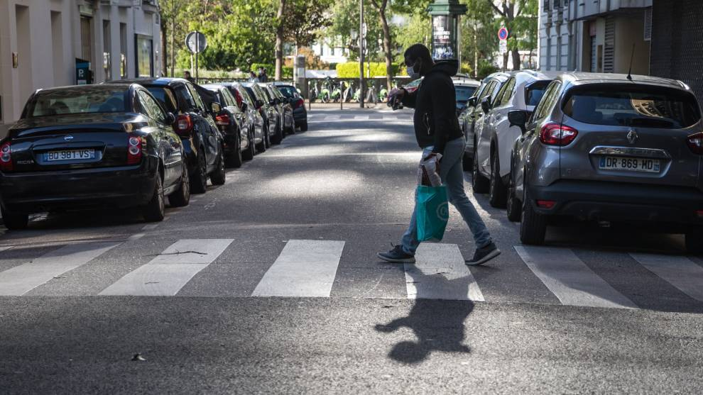 Un hombre camina por las calles de París con la mascarilla preceptiva