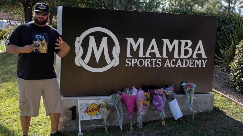 Fanático junto al cartel de Mamba Sports Academy