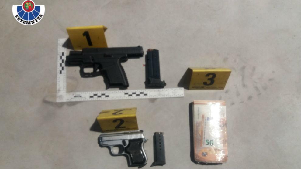 Las dos pistolas y el fajo de billetes confiscados por la Ertzaintza.