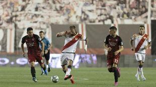 Esteban Saveljich, entre dos jugadores del Mirandés en Vallecas