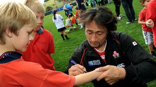 Ono firma un autógrafo en un brazo.