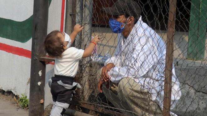 Un hombre habla con un niño a través de un verja.
