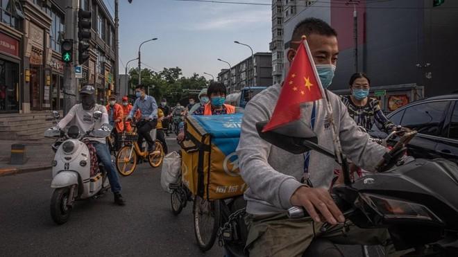 Personas con mascarilla en motocicleta en Beijing.