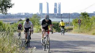 Ciclistas por Madrid con las cuatro torres de la capital al fondo.