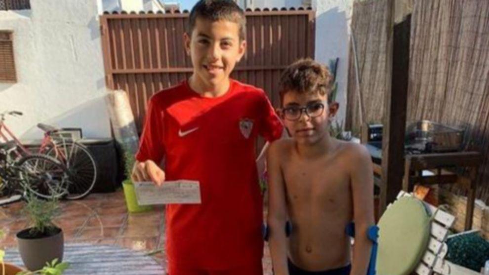 Francis, alevín del Sevilla, muestra el cheque donado a su vecino y...