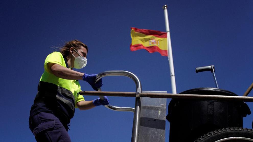 Un empleado de la limpieza con una bandera a media asta al fondo.