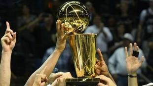 El trofeo de la campeón de la NBA, sujetado por varios jugadores.