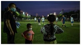 Ciudadanos de Wuhan juegan al fútbol en la calle durante la...