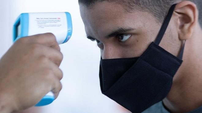 Un hombre con mascarilla se somete a un examen de temperatura en...