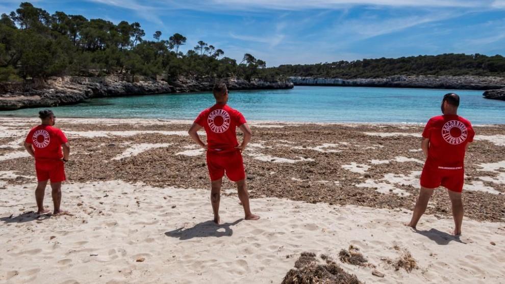 Tres socorristas observan la playa vacía de bañistas.