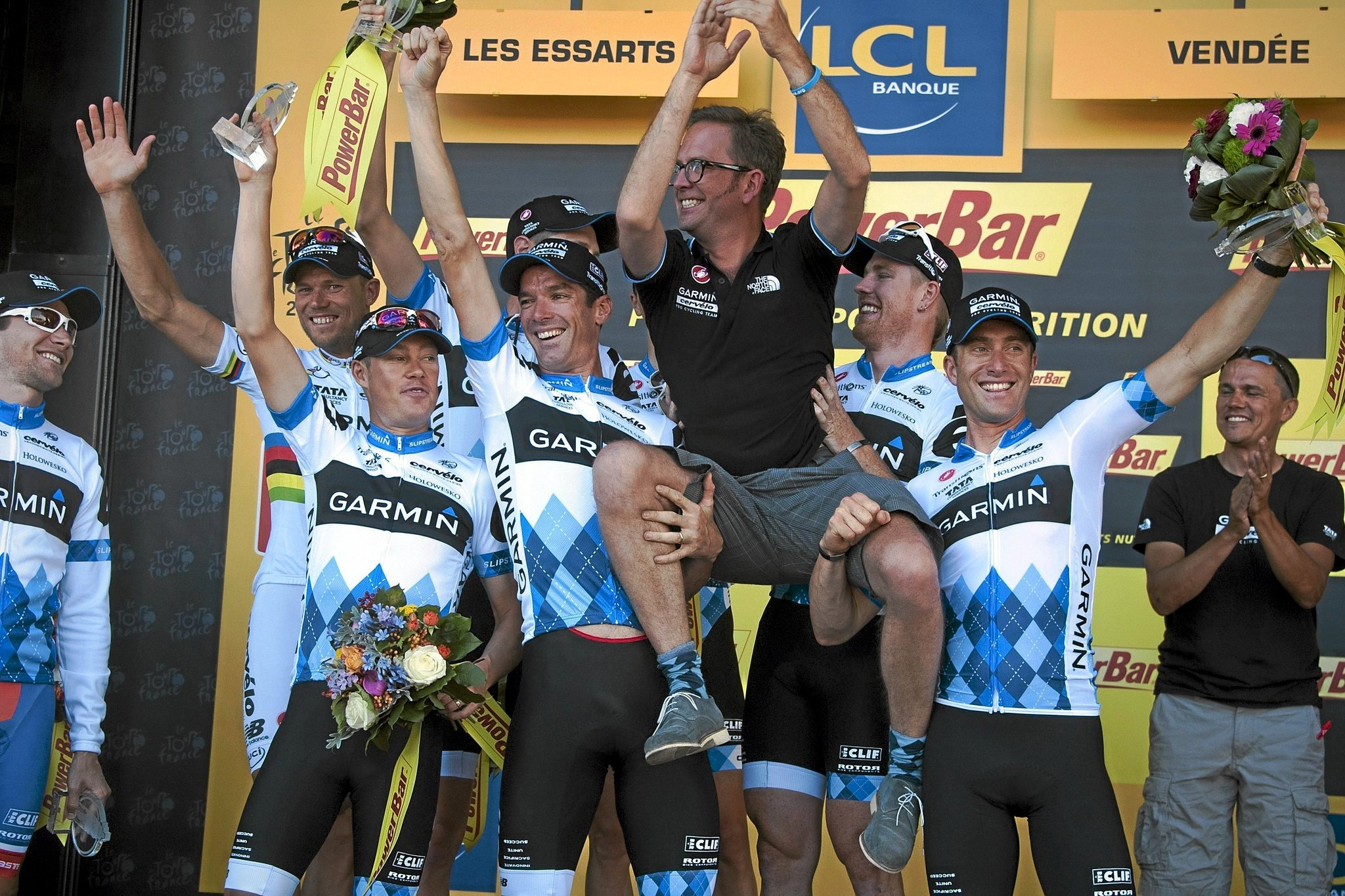 New Yellow jersey of Overall leader, Norwegias Thor Hushovd (2ndL), poses with teammates to celebrate the best team podium as they carry their sport director Jonathan lt;HIT gt;Vaughters lt;/HIT gt;, after winning the 23 km team time-trial and second stage of the 2011 Tour de France cycling race run around Les Essarts, western France, on July 3, 2011. AFP PHOTO / PASCAL PAVANI