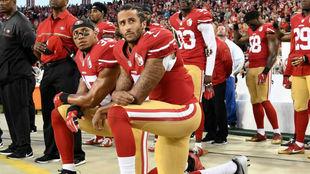 Colin Kaepernick, arrodillado mientras sonaba el himno estadounidense,...