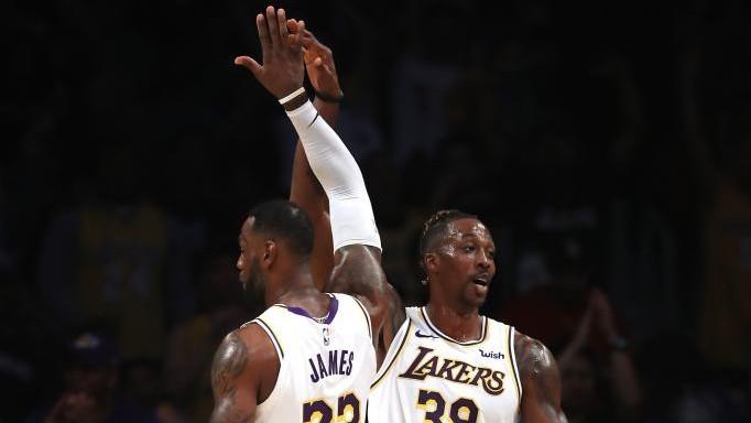 LeBron James y Dwight Howard chocan las manos en un partido de los...