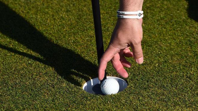Un jugador recoge una bola durante un torneo