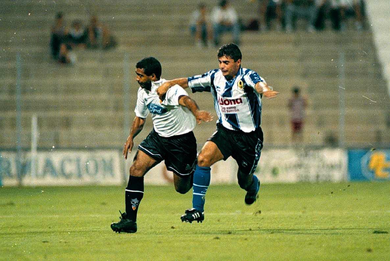Los dos jugadores corren y se agarran para llegar a la pelota