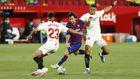 Diego Carlos y Reguilón tratan de frenar a Messi.