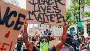 Hamilton sostiene una pancarta durante la manifestación del domingo...