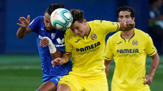 Pau Torres y En-Nesyri pugnan por golpear la pelota con la cabeza.