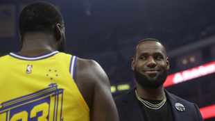 Draymond Green y LeBron James conversan durante un partido