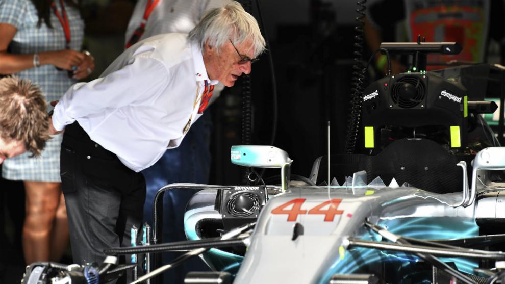 Ecclestone inspecciona el coche de Hamilton.
