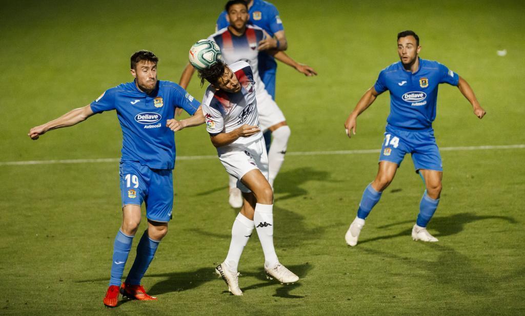 Álex Alegría, autor del gol del empate, disputa un balón aéreo con...