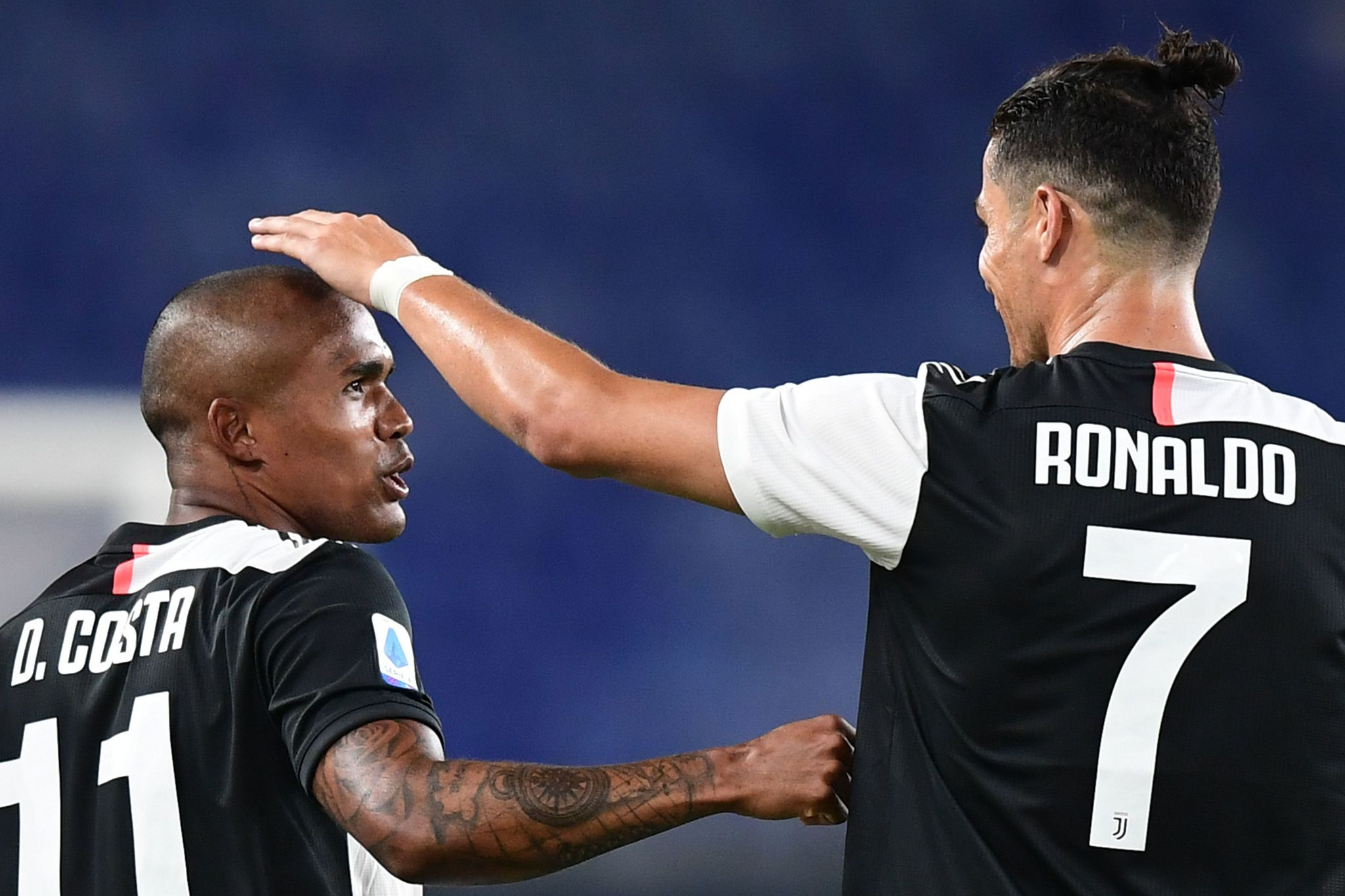 Juventus Brazilian forward lt;HIT gt;Douglas lt;/HIT gt; lt;HIT gt;Costa lt;/HIT gt; (L) celebrates with Juventus Portuguese forward Cristiano Ronaldo after scoring during the Italian Serie A football match Genoa vs Juventus played on June 30, 2020 behind closed doors at the Luigi-Ferraris stadium in Genoa, as the country eases its lockdown aimed at curbing the spread of the COVID-19 infection, caused by the novel coronavirus. (Photo by Miguel MEDINA / AFP)
