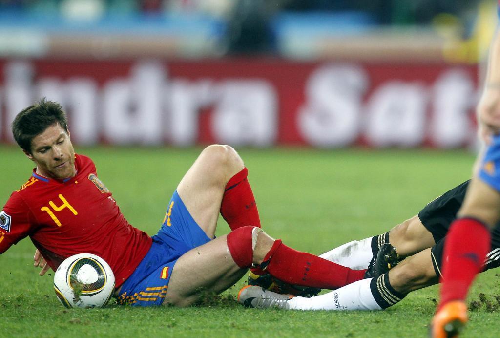 Xabi Alonso disputando en el suelo un balón frente a Alemania.