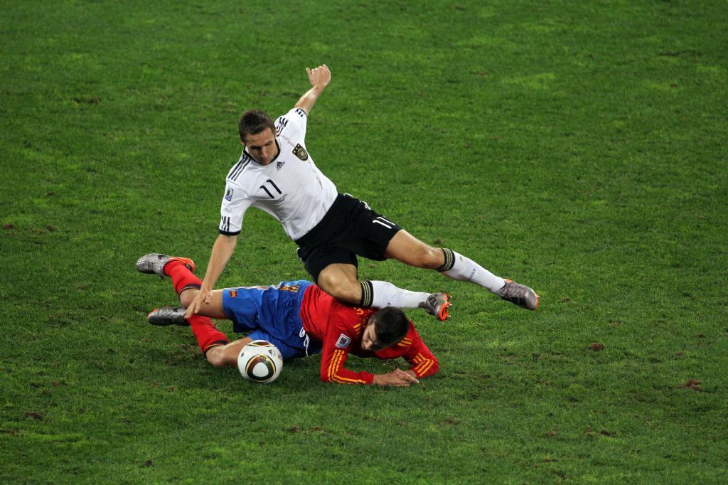 Piqué en el suelo disputando un balón con Klose.