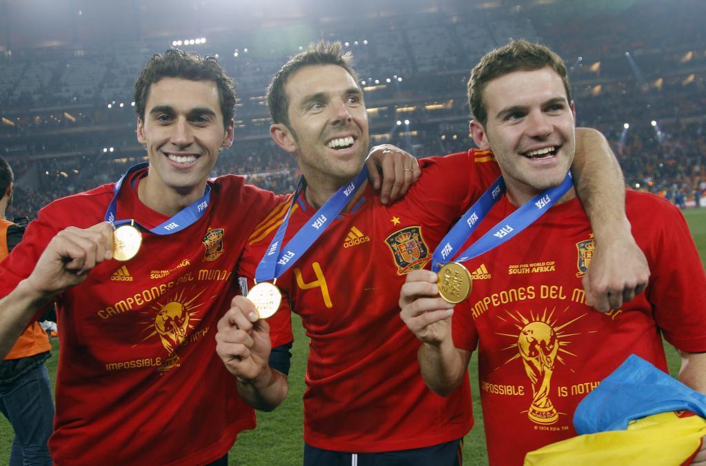 Carlos Marchena posando en el centro con la medalla junto a Arbeloa y Mata.