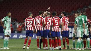 Los jugadores del Atlético rodean al colegiado tras la expulsión de...
