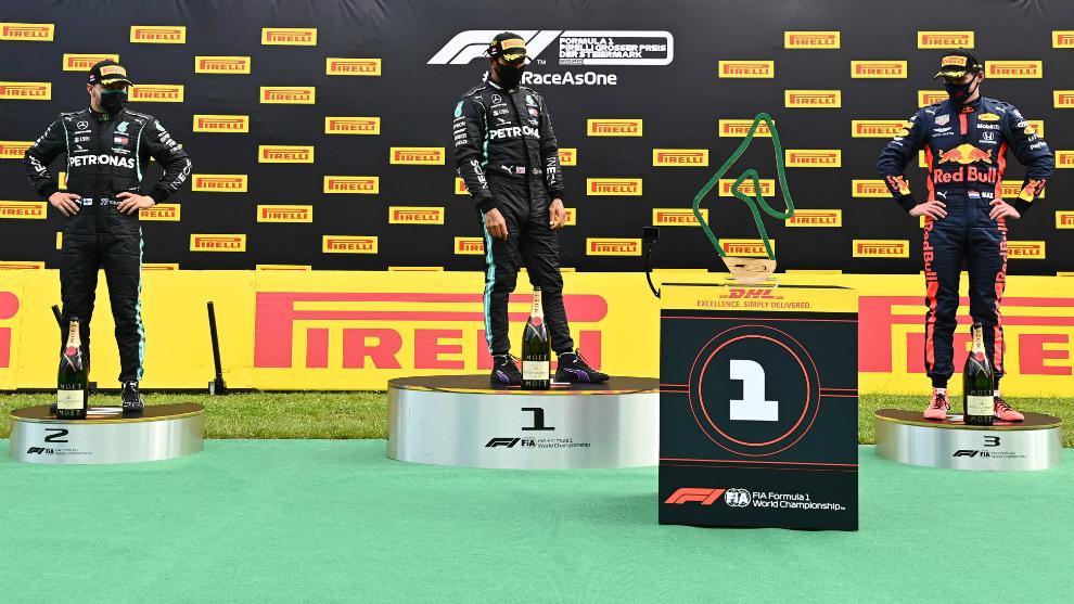 Hamilton va a recibir su trofeo, flanqueado por Bottas y Verstappen.