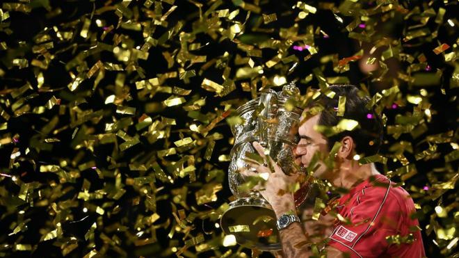 Roger Federer besa el trofeo que le acredita como ganador del Torneo...