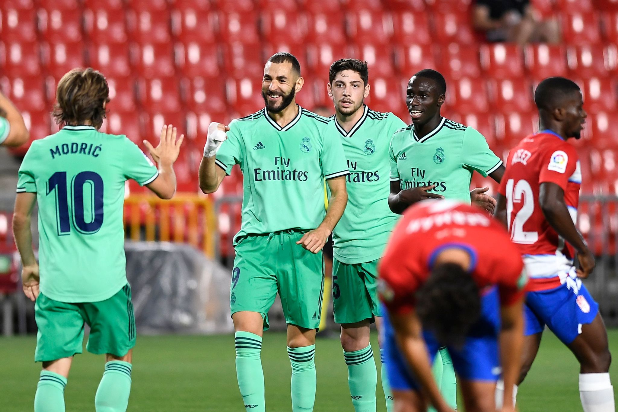 Real Madrids French forward Karim lt;HIT gt;Benzema lt;/HIT gt; (2L) celebrates after scoring during the Spanish league football match Granada FC vs Real Madrid CF at Nuevo Los Carmenes stadium in Granada on July 13, 2020. (Photo by JORGE GUERRERO / AFP)