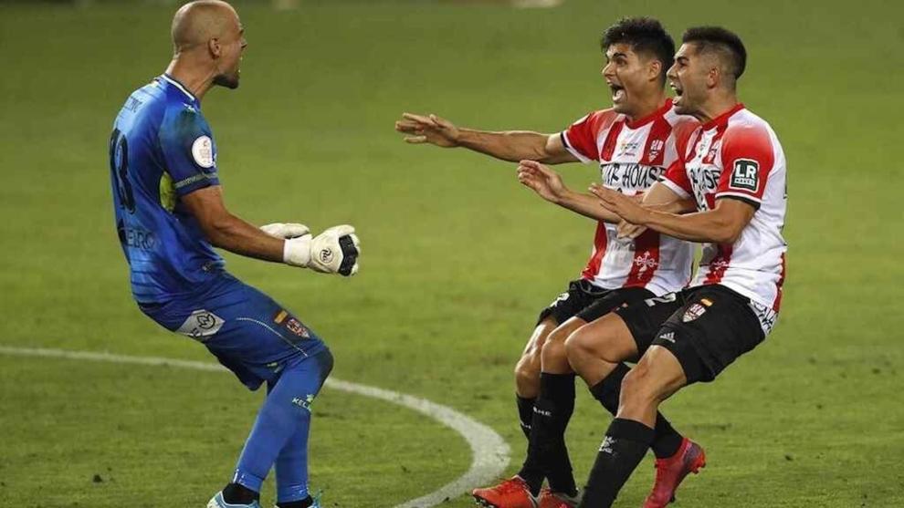 Rubén Miño celebra con dos compañeros el ascenso tras la tanda de...