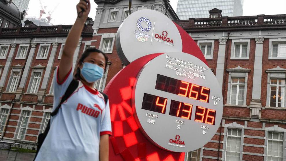 Una mujer con mascarilla posa delante del cartel que indica los días...