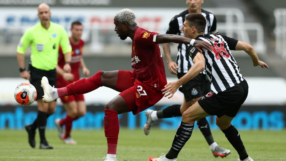 Liverpools Belgium striker Divock lt;HIT gt;Origi lt;/HIT gt; (C) controls the ball next to Newcastle Uniteds Argentinian defender Federico Fernandez (R) during the English Premier League football match between Newcastle United and Liverpool at St James Park in Newcastle-upon-Tyne, north east England on July 26, 2020. (Photo by Jan Kruger / POOL / AFP) / RESTRICTED TO EDITORIAL USE. No use with unauthorized audio, video, data, fixture lists, club/league logos or live services. Online in-match use limited to 120 images. An additional 40 images may be used in extra time. No video emulation. Social media in-match use limited to 120 images. An additional 40 images may be used in extra time. No use in betting publications, games or single club/league/player publications. /