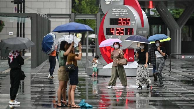 Personas con mascarilla pasando delante del famoso reloj de Tokio que...